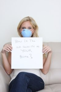 woman-holding-sign-asking-how-is-the-air-quality-in-your-home