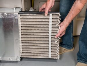 mans-hands-pulling-out-dirty-air-filter