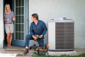 technician-working-on-outside-ac-unit-with-homeowner-in-background